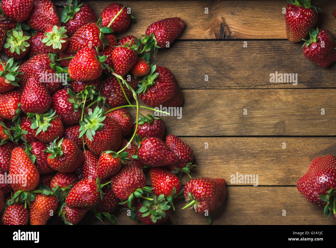 Summer fruit food frame. Strawberries over natural wooden background. Top view, copy space - Stock Image