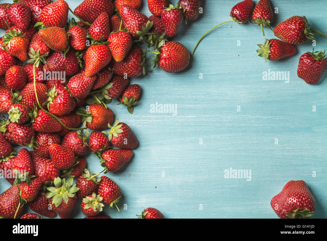 Summer fruit food frame. Strawberries over turquoise blue painted wooden background. Top view, copy space - Stock Image
