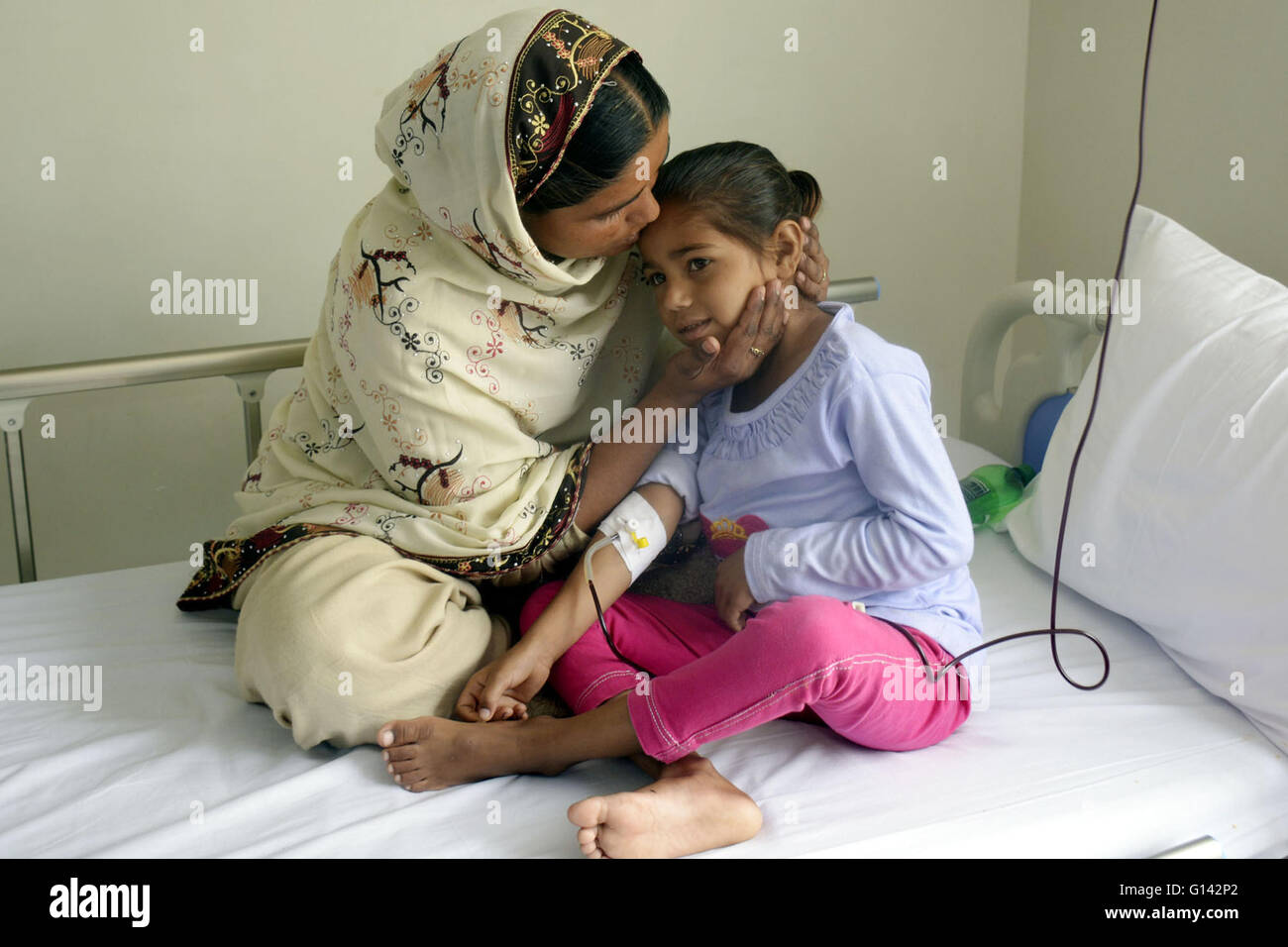 Lahore, Pakistan. 8th May, 2016. A mother takes care of her daughter suffering from thalassemia during treatment - Stock Image