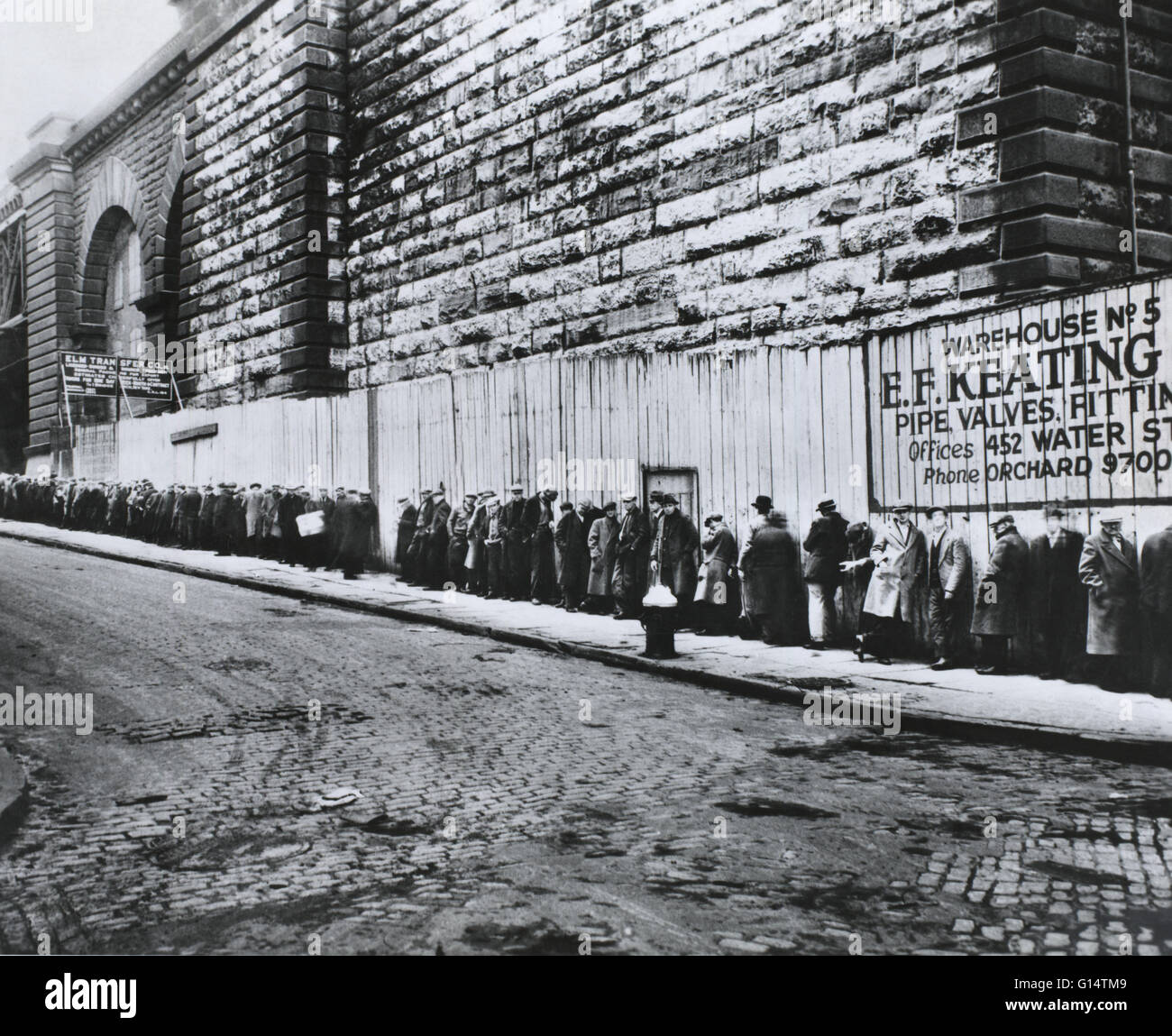 New York, New York. Bread line beside the Brooklyn Bridge approach during the the Great Depression between 1930 - Stock Image