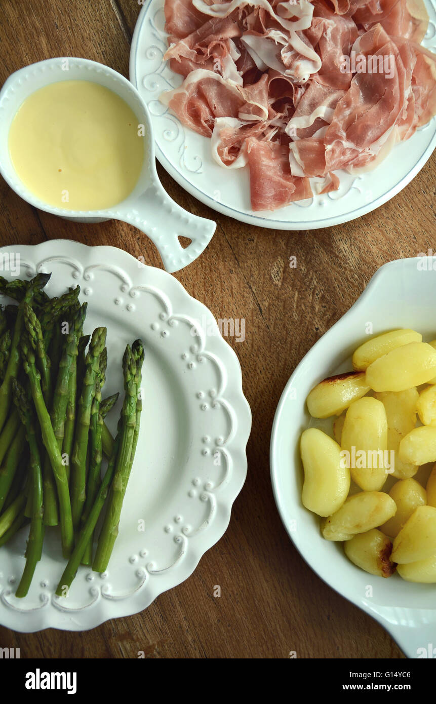 Green asparagus with prosciutto and new potatoes served with sauce hollandaise on the wooden table - Stock Image