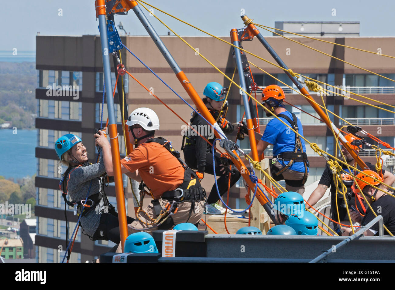 Detroit, Michigan - People rappel down a 25-story building as a fundraiser to benefit charities in Detroit and Nepal. - Stock Image
