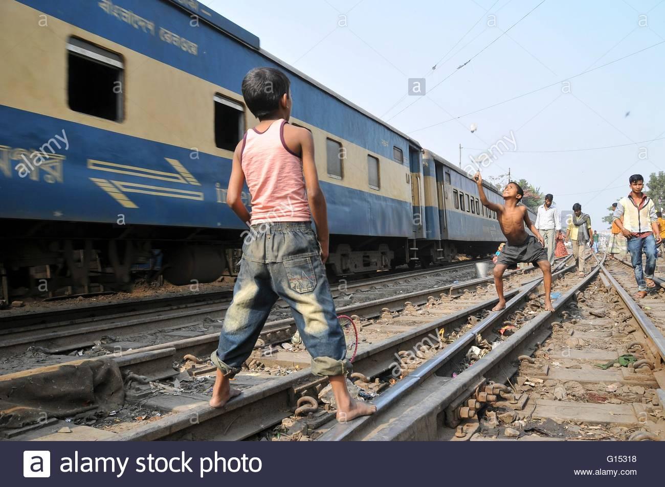 Bangladesh, Dhaka, children playing on rail tracks - Stock Image