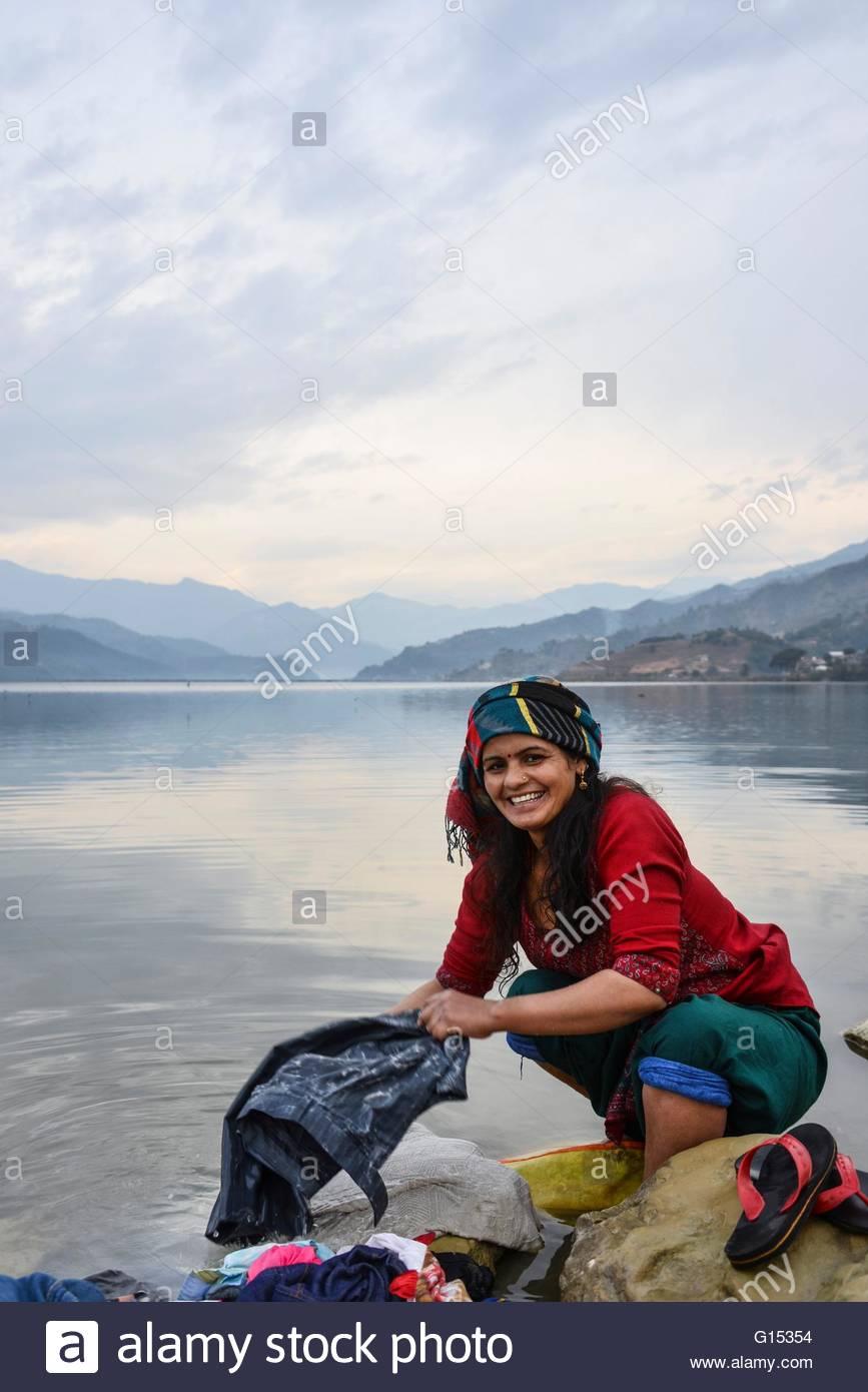 Nepal, Pokhara lake, woman washing clothes - Stock Image