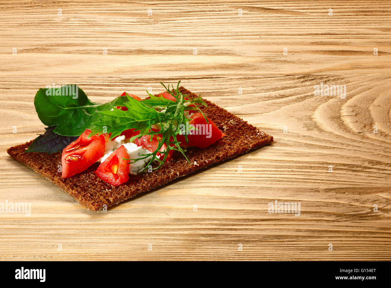 Bread crisp (crispbread open-faced sandwich) with chopped heirloom tomato, cream cheese and leafy green salad on - Stock Image