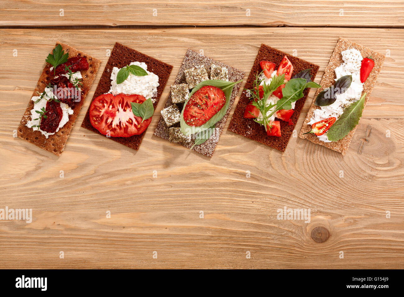 Different bread crisps (crispbread open-faced sandwiches) with both fresh and dried heirloom tomatoes, cream cheese - Stock Image