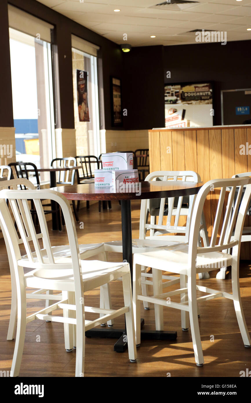 Dining setting in Krispy Kreme cafe with white wooden chairs and brown table - Stock Image