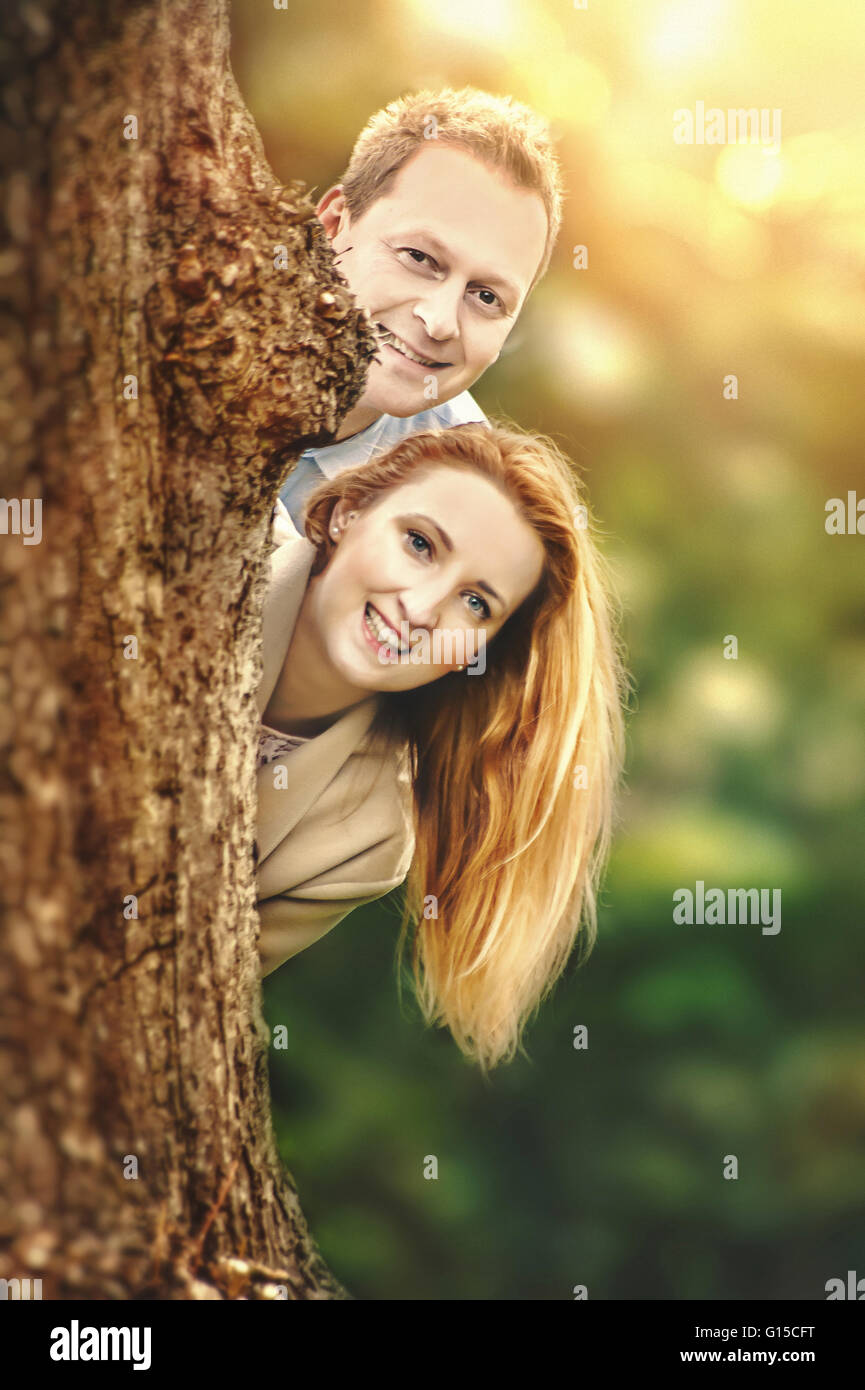 happy young couple standing behind tree and having fun - Stock Image