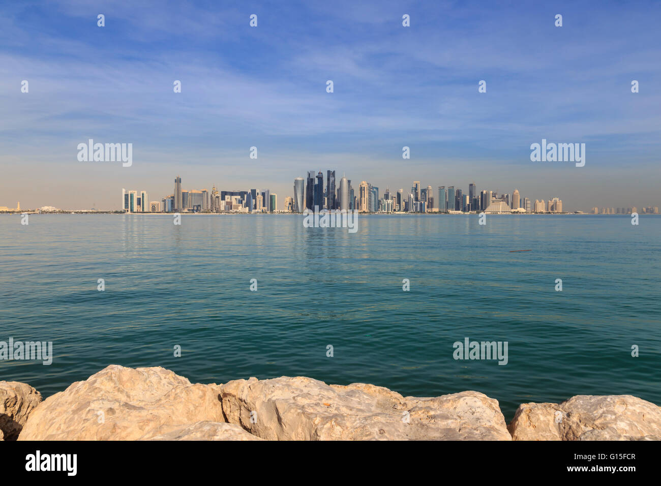 Modern city skyline of West Bay, across the calm turquoise waters of Doha Bay, from the Dhow Harbour, Doha, Qatar, - Stock Image