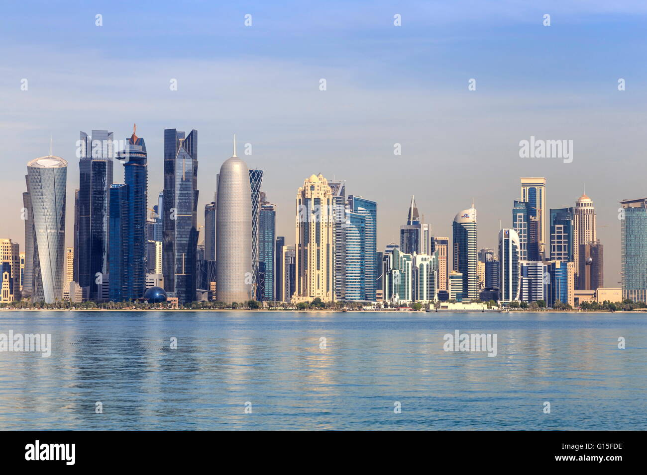 Modern city skyline of West Bay, across the calm waters of Doha Bay, from the Dhow Harbour, Doha, Qatar, Middle - Stock Image