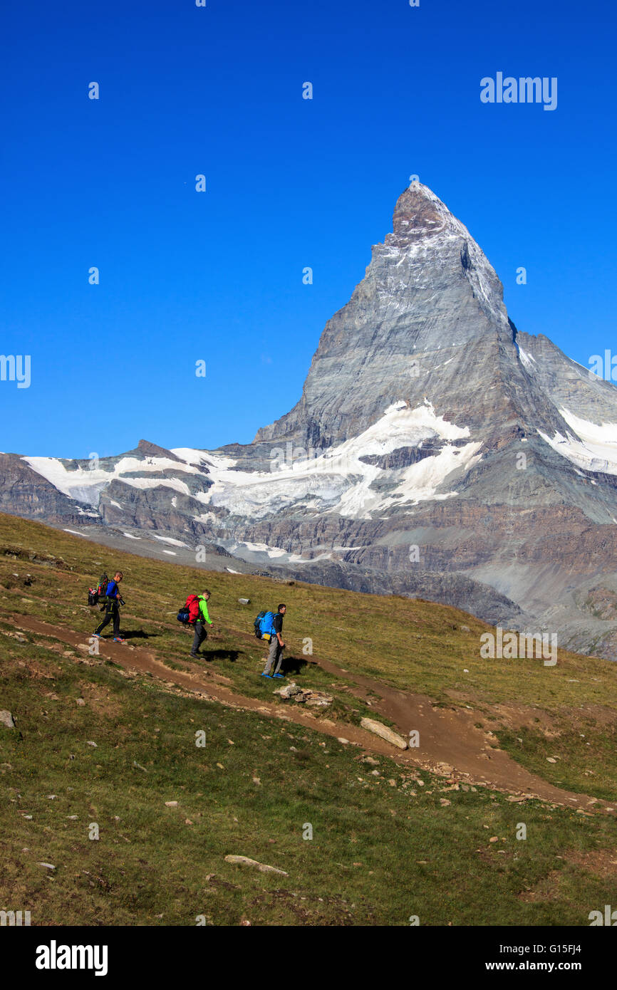 Hikers proceed with the Matterhorn in background in a clear summer day, Gornergrat, Canton of Valais, Swiss Alps, - Stock Image