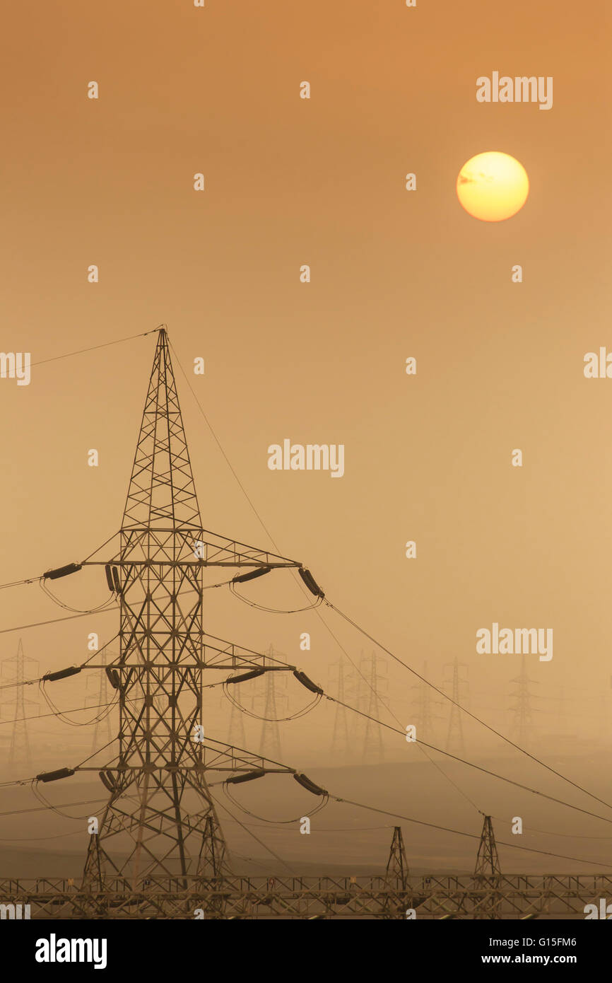 Power pylons stretch into the distance, sun rises through air thick with sand, Suez Canal, Port Said, Egypt, North - Stock Image
