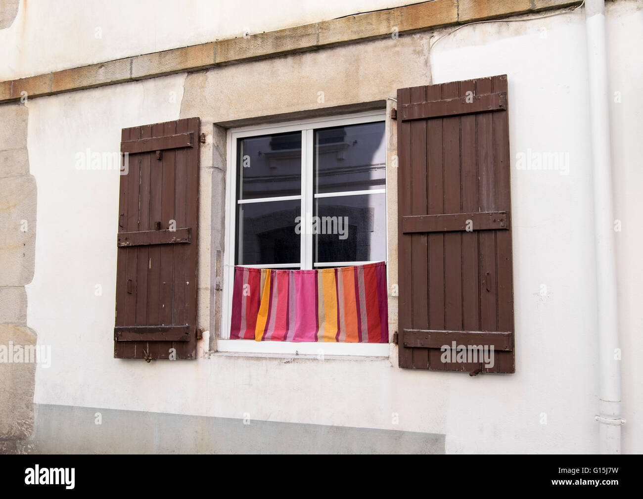 Window with brown wooden shutters and curtain - Stock Image