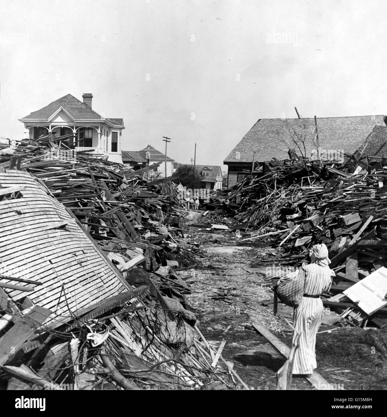 A woman walks through an opened passageway in the debris, North on 19th Street, Galveston, Texas The Hurricane of - Stock Image