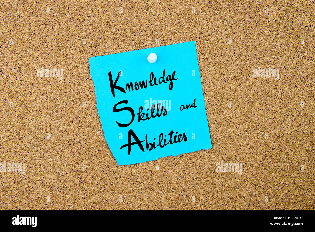 Business Acronym KSA as Knowledge, Skills and Abilities written on blue paper note pinned on cork board with white - Stock Image