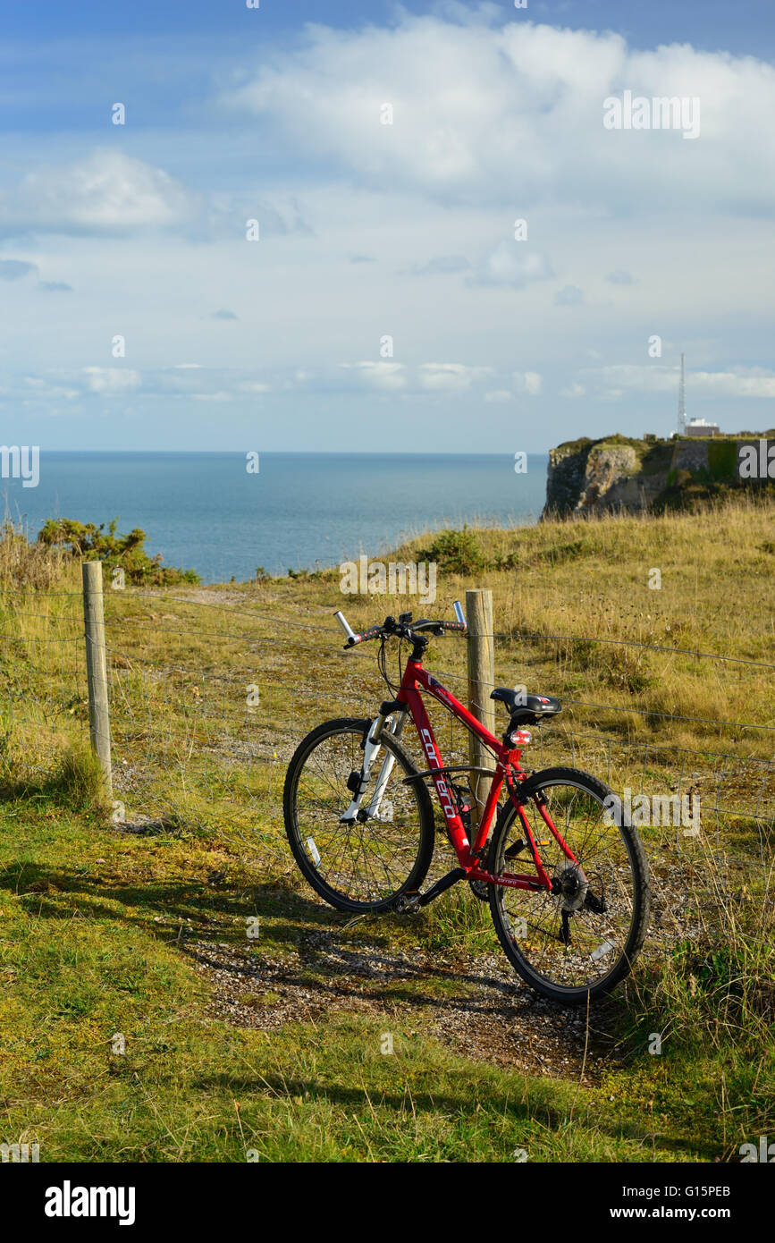 A bicycle secured to a fence post overlooking the sea at Berry Head. - Stock Image