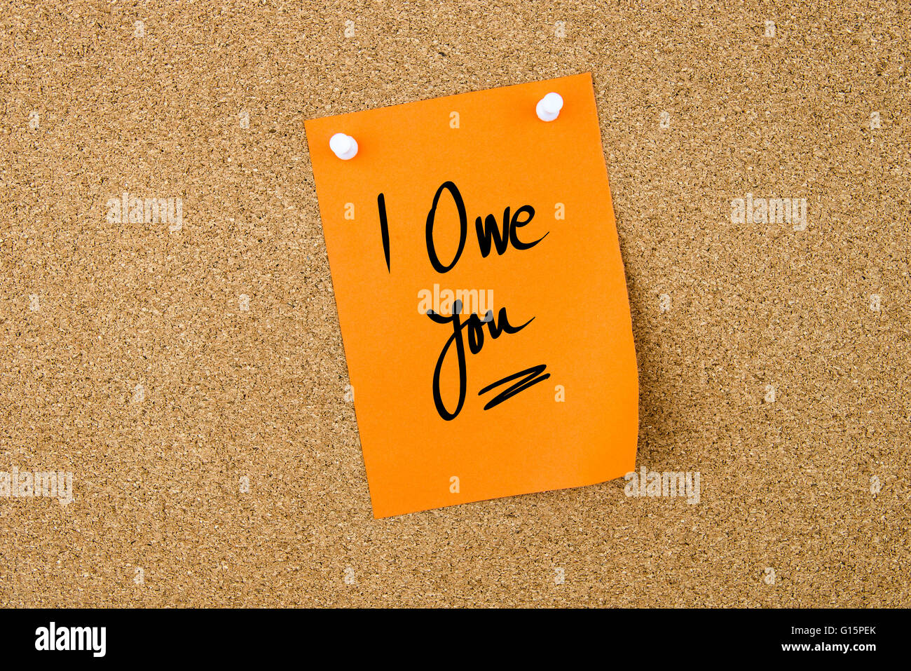 I Owe You written on orange paper note pinned on cork board with white thumbtacks, copy space available - Stock Image
