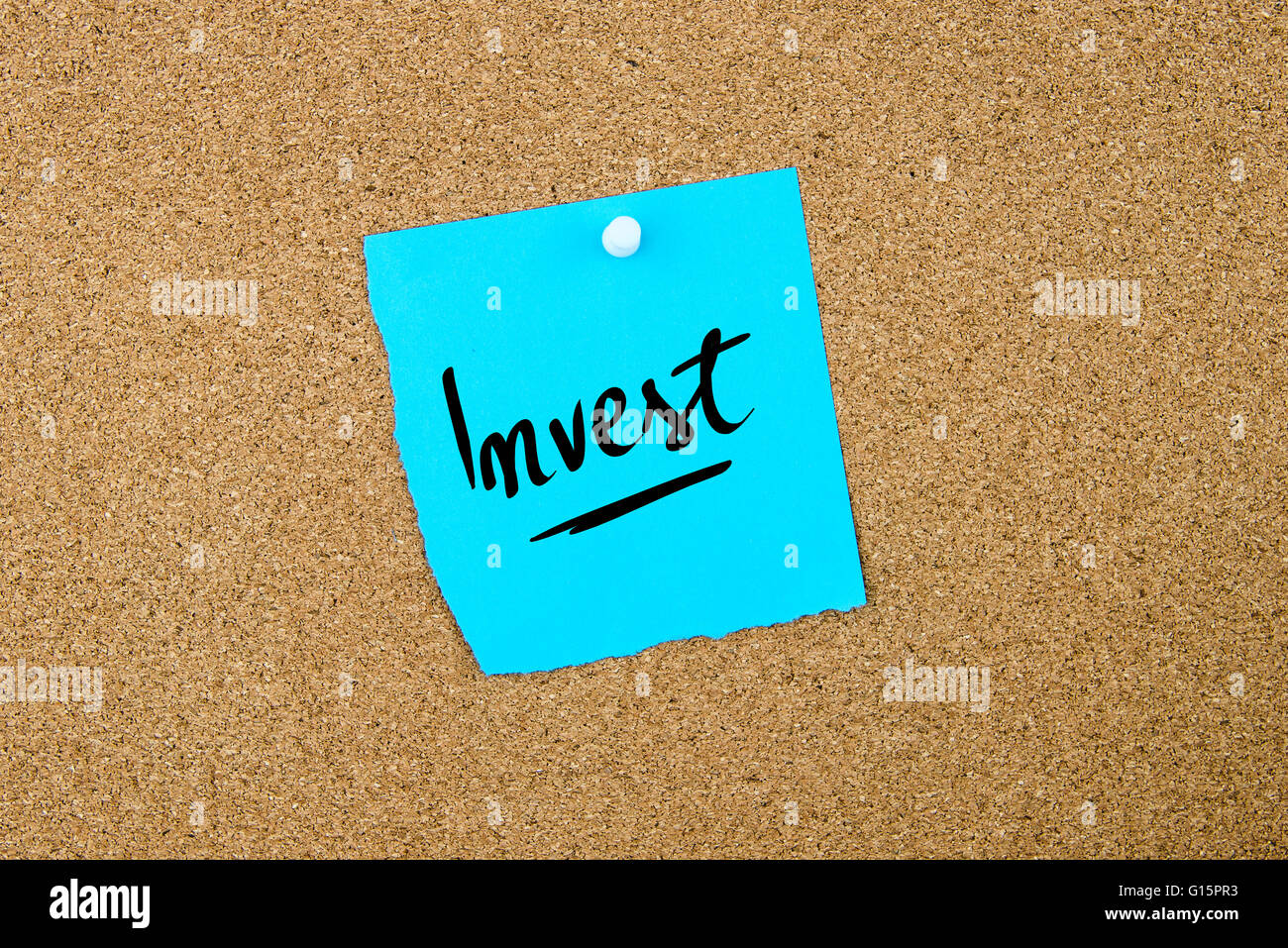 Invest written on blue paper note pinned on cork board with white thumbtacks, copy space available - Stock Image