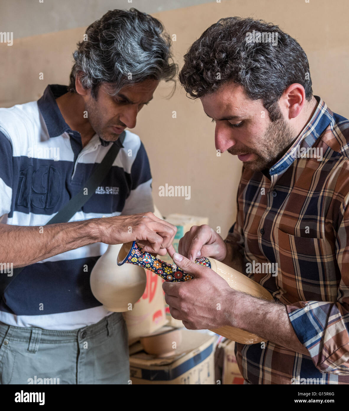 Hojjat explains that his brother developed the patent for a paint that does not run out of the lines on the pottery - Stock Image