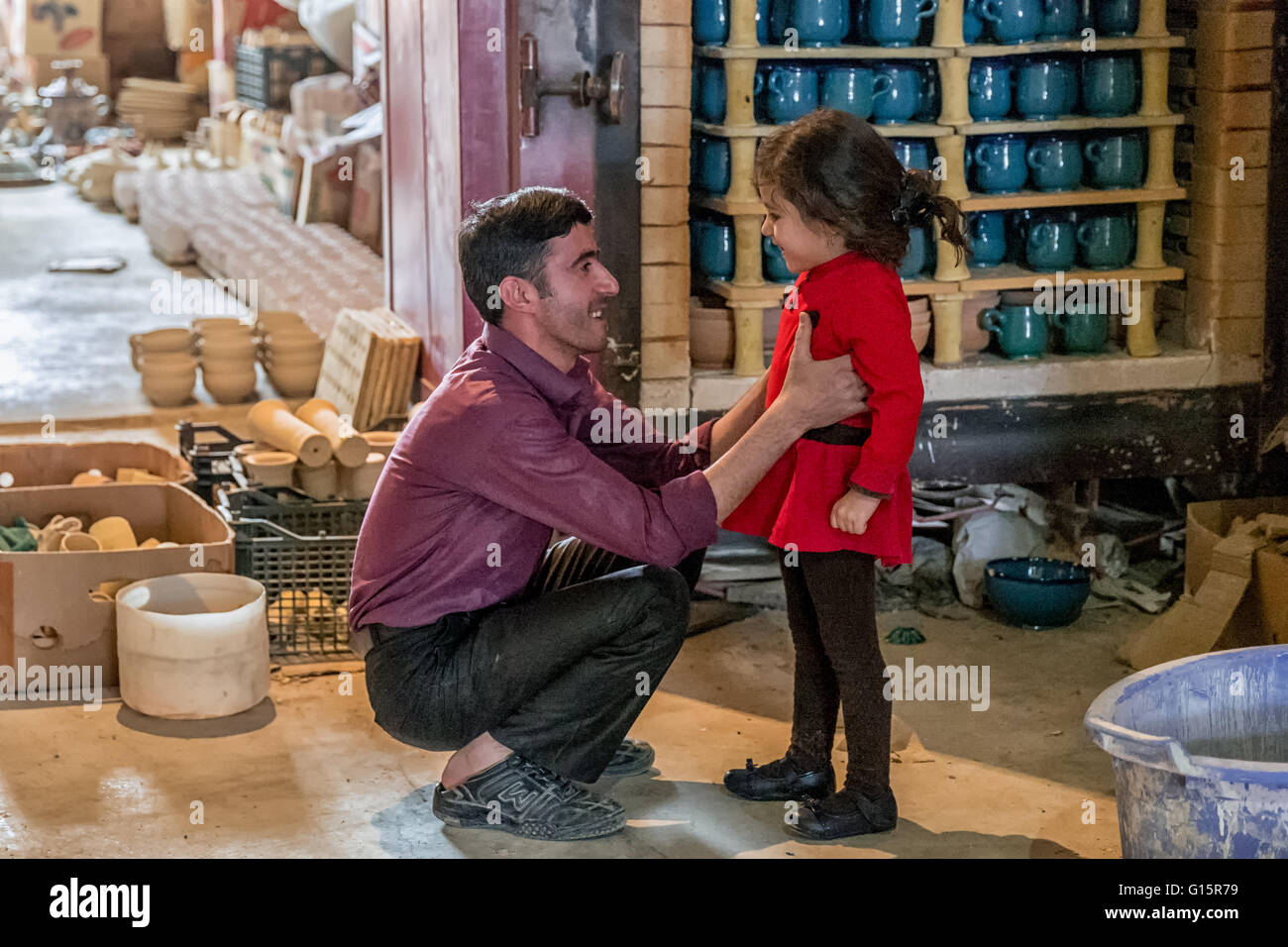 Narges with her uncle in her father's pottery workshop in Lalejin, Hamadan Province, Iran, famous throughout - Stock Image