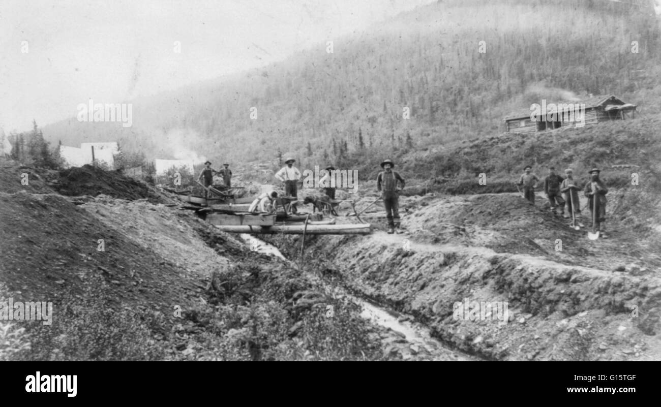 Gold miner's camp and large log cabin on hillside in El Dorado, California circa 1848-53. Prospectors with shovels - Stock Image