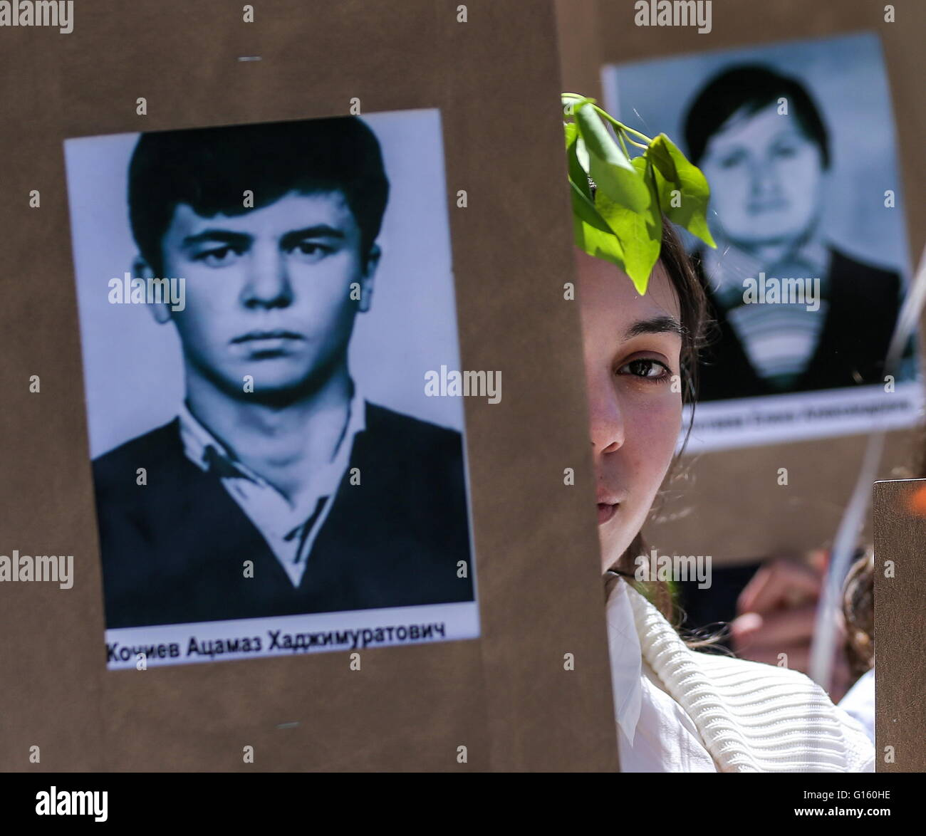 TSKHINVAL, SOUTH OSSETIA. 9 MAY, 2016. A young South Ossetian woman with a photograph of her family member who fought - Stock Image