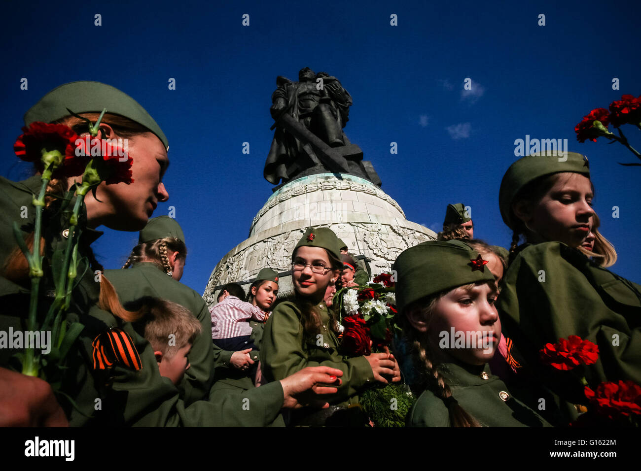 Berlin, Germany. 9th May, 2016. People wearing Soviet army uniforms and holding flowers gather in front of a Soviet Stock Photo