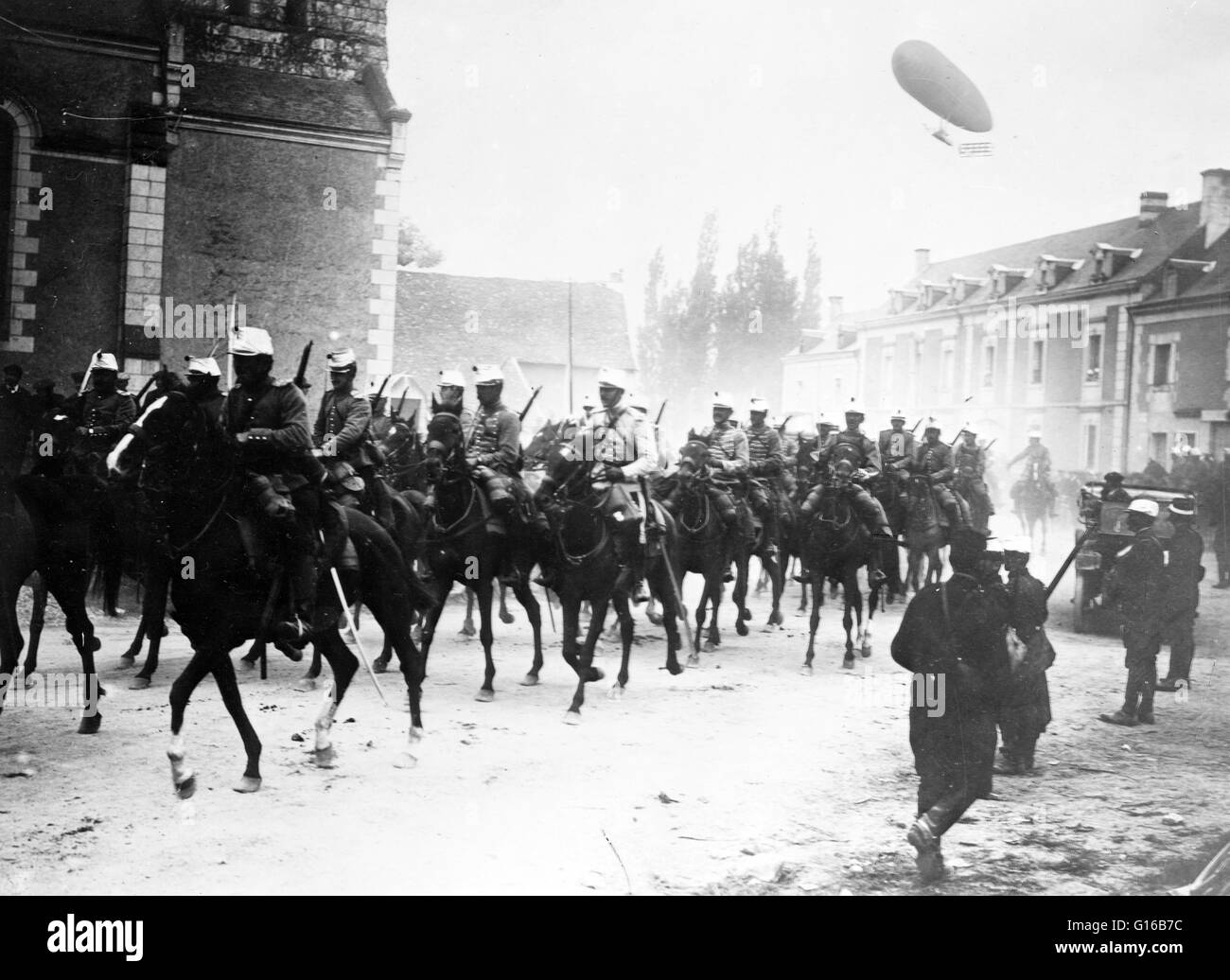 French soldiers on horseback in street, with an airship flying in air behind them during World War I. Cavalry or Stock Photo
