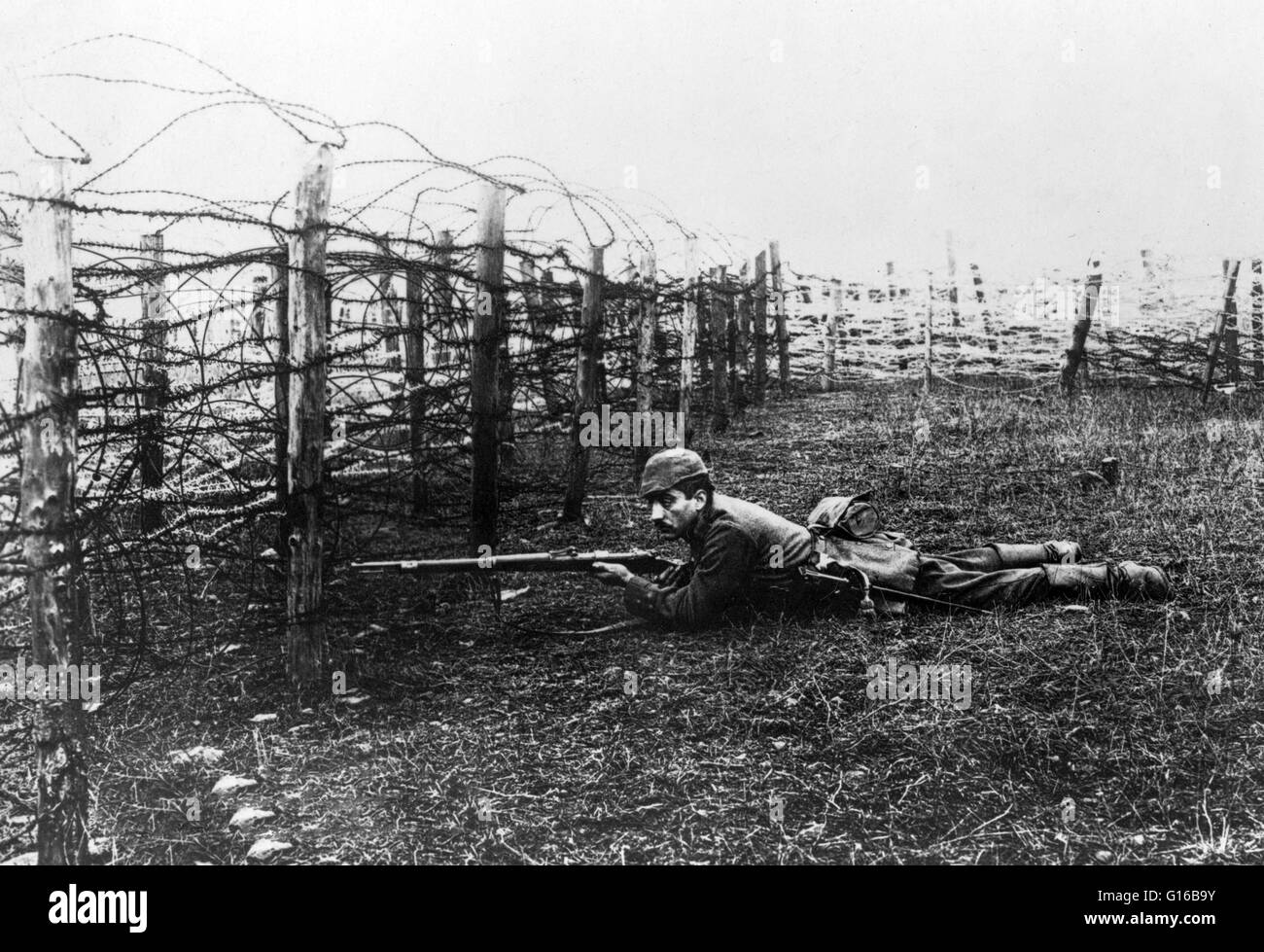 German sniper laying on ground near barbed wire defenses. Throughout World War I, snipers were often used in the - Stock Image