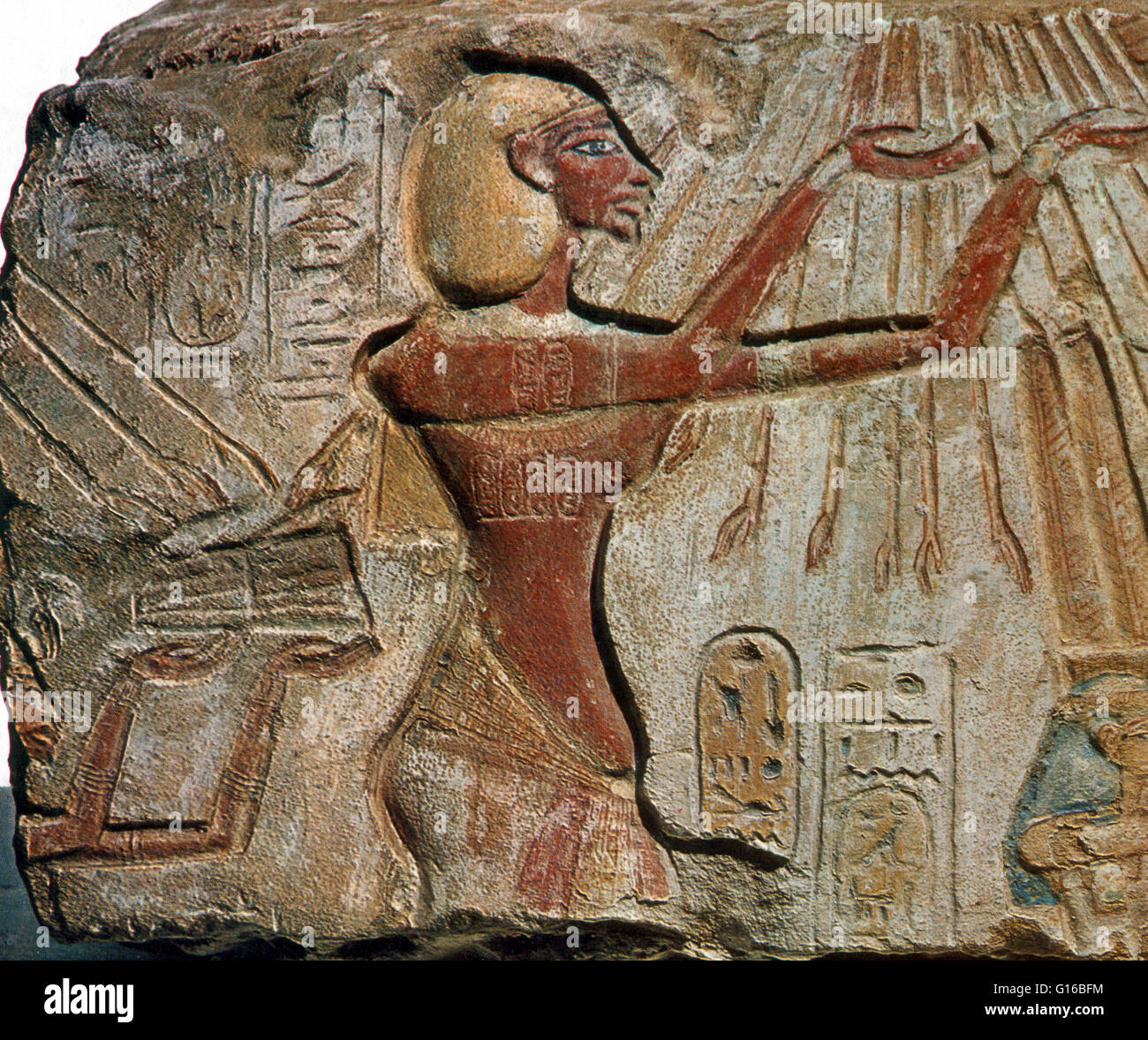 Caption: 'Bas relief, Akhenaten raises his hands to worship the sun, whose descending rays end in hands, circa - Stock Image