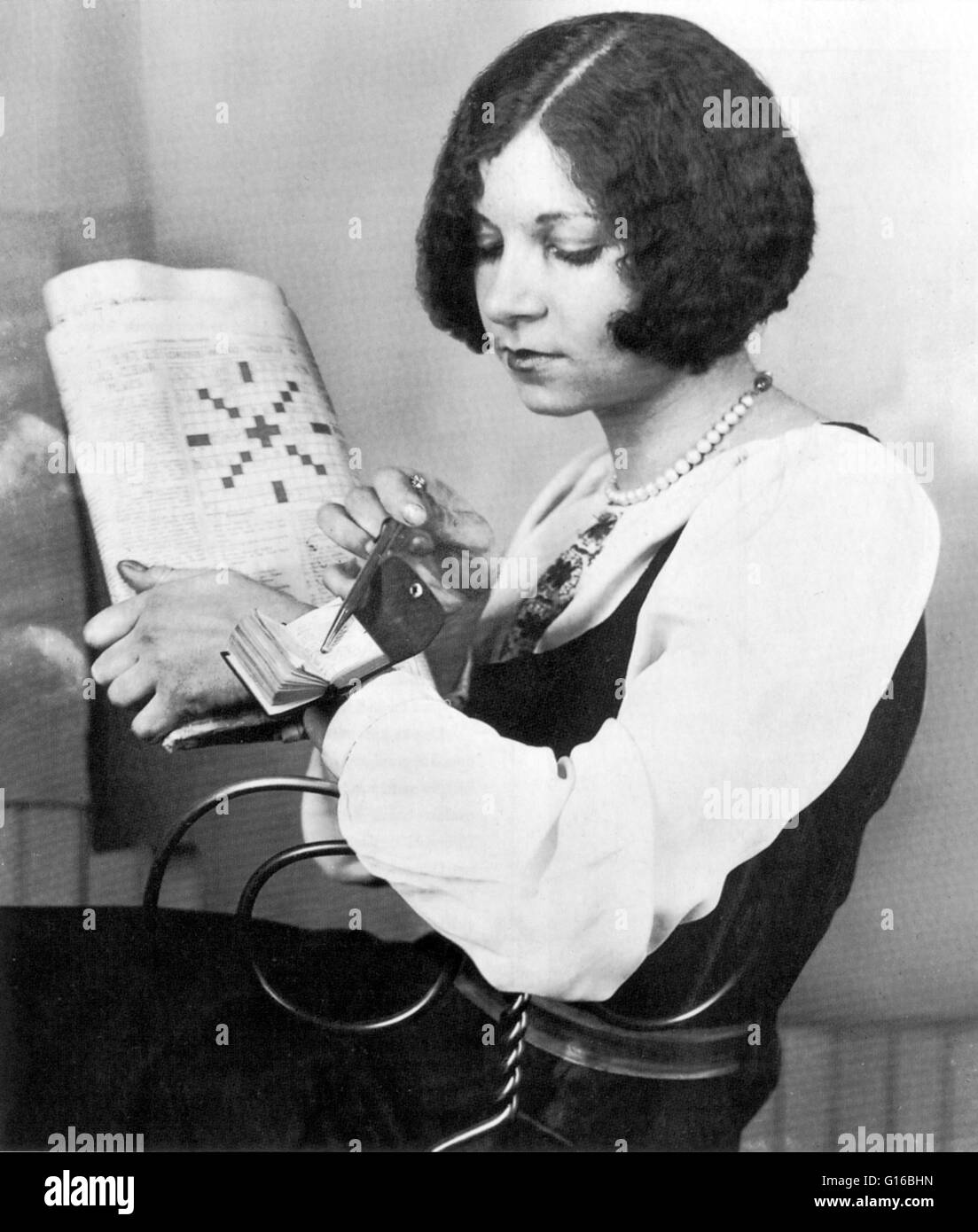 The 1920s brought a crossword puzzle fad to the United States. This young woman looks up 'Egyptian Sun God' - Stock Image