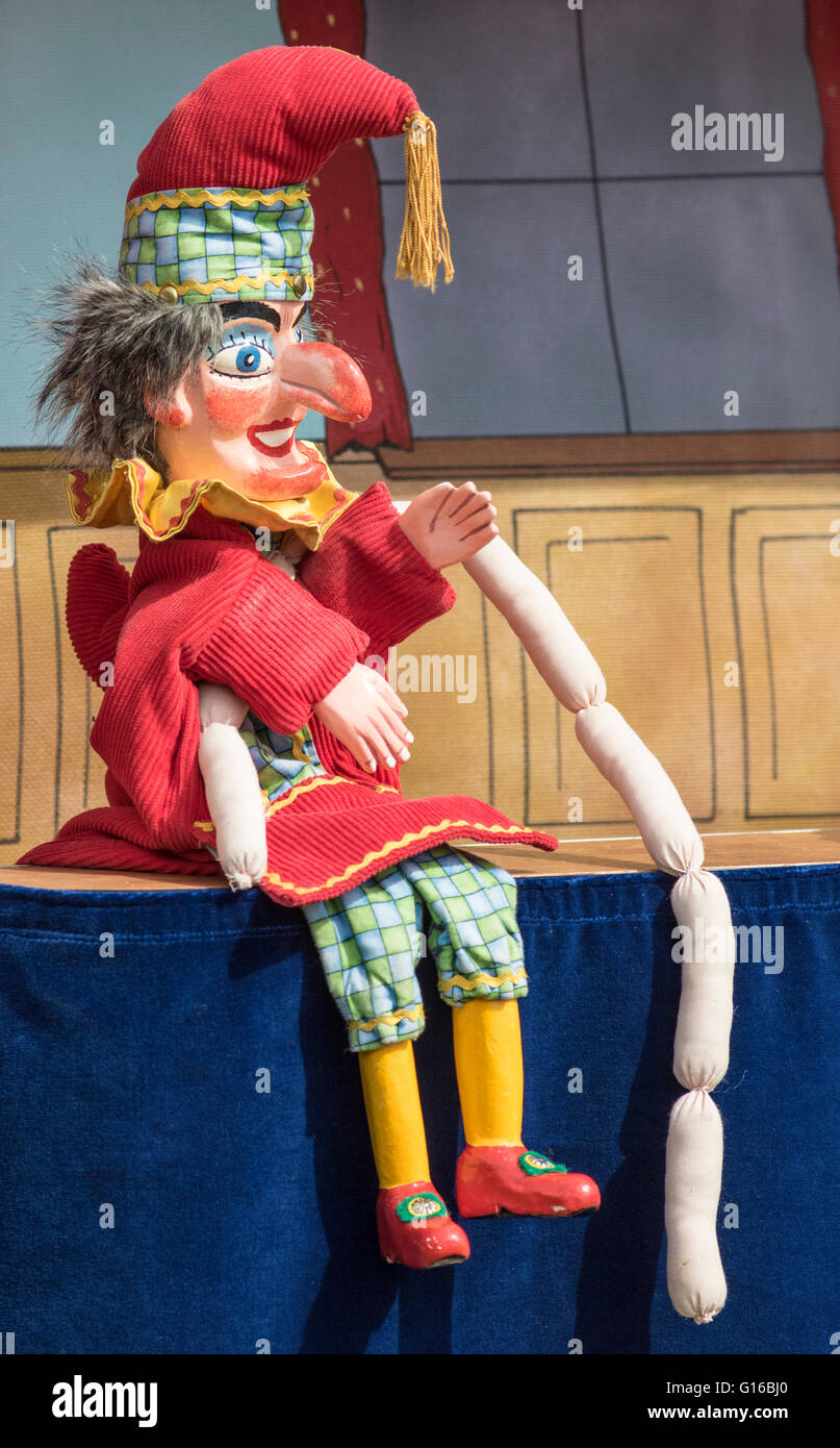 Mr Punch with a string of sausages at a Punch and Judy show - Stock Image
