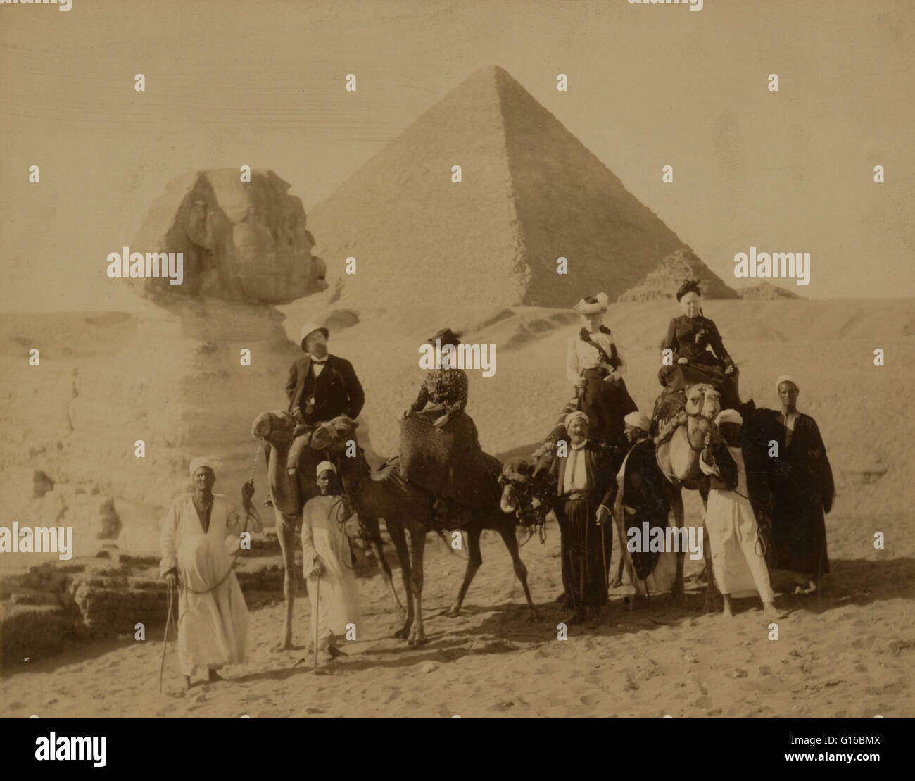 Entitled: 'Three women and a man in western attire, seated on camels, several local men stand before the camels - Stock Image