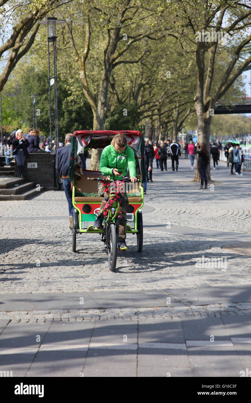 Riksha rider in Cologne, Germany, operating mobile phone Stock Photo