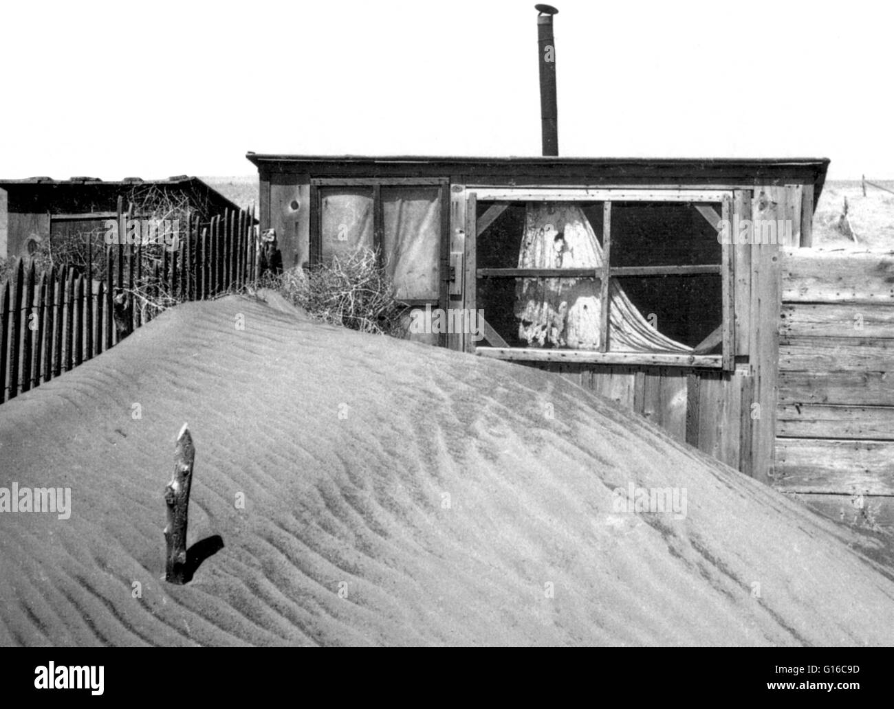 Windblown sand blocks the door of a shed Cimarron County, Oklahoma. Piling up around a house one day, sand would - Stock Image