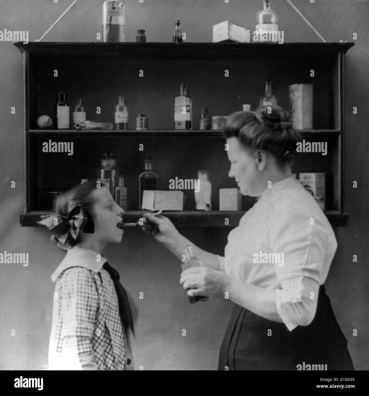Woman spoon feeding medicine to a young girl; various medicines on display on shelves next to woman and child, 1915. - Stock Image