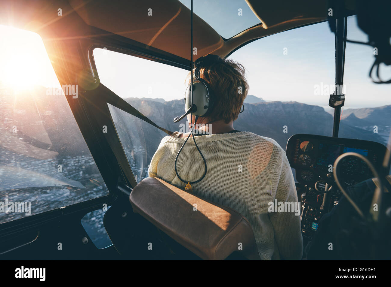 Rear view of female tourist on helicopter looking out of the window. Helicopter passenger admiring the view. - Stock Image