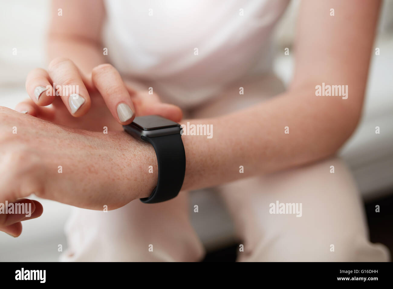Closeup shot of caucasian female checking time on her smart watch. Focus on wrist watch and hands. - Stock Image