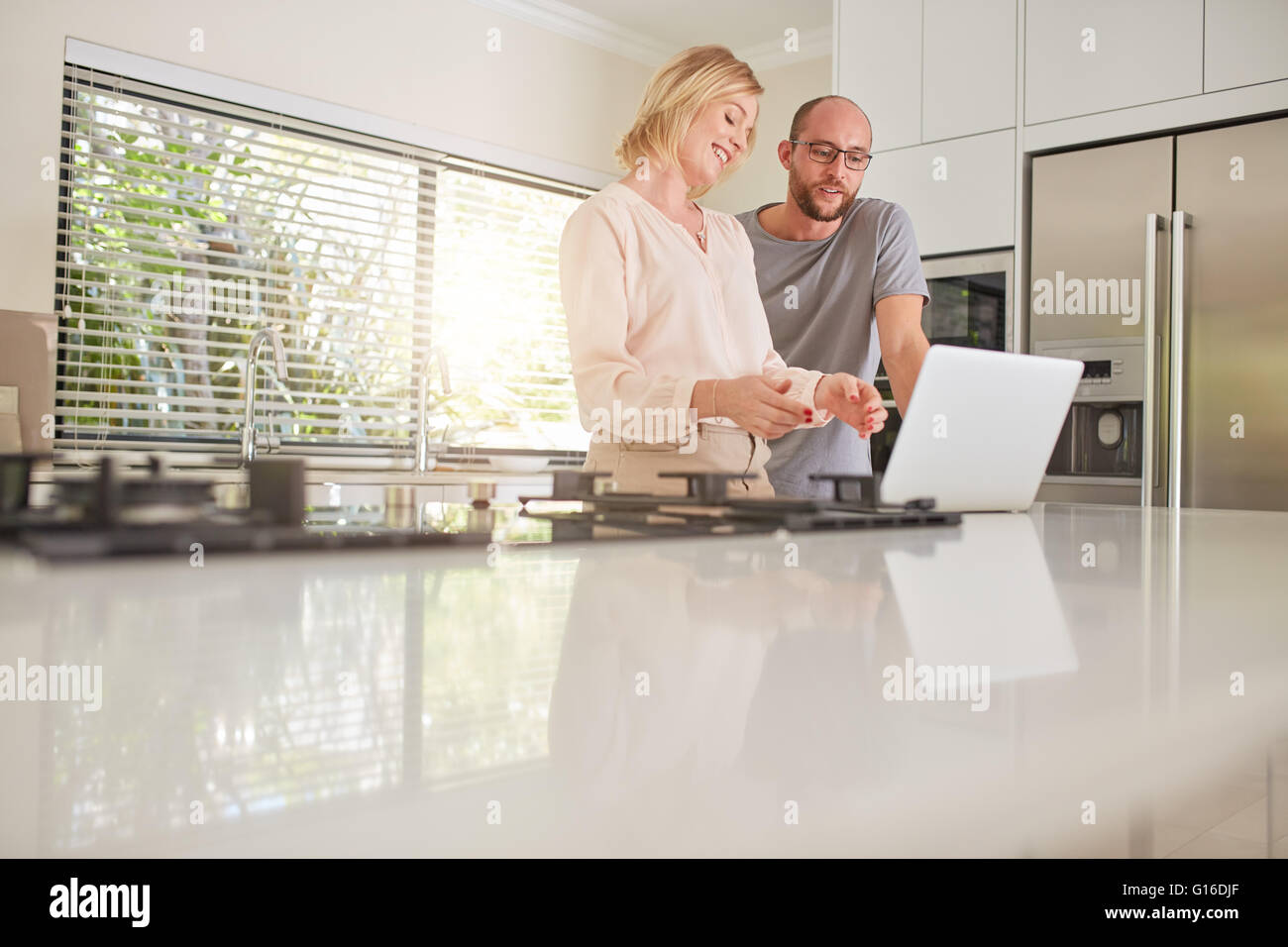 Indoor shot of a happy couple using laptop computer in the kitchen. Woman showing something on laptop to man. - Stock Image