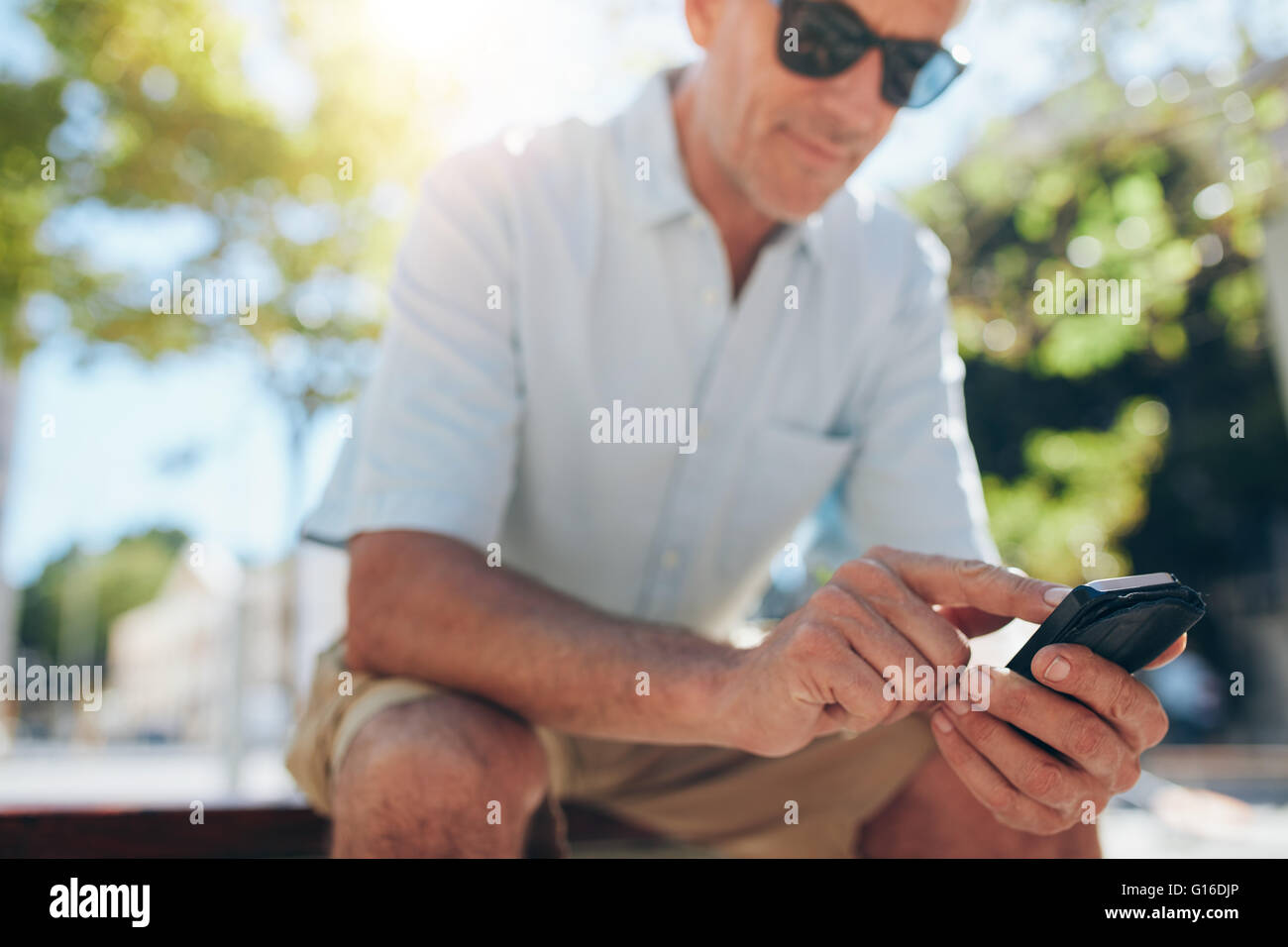 Close up portrait of senior man using cell phone while sitting on a bench in the city on a sunny day. Focus on hands - Stock Image