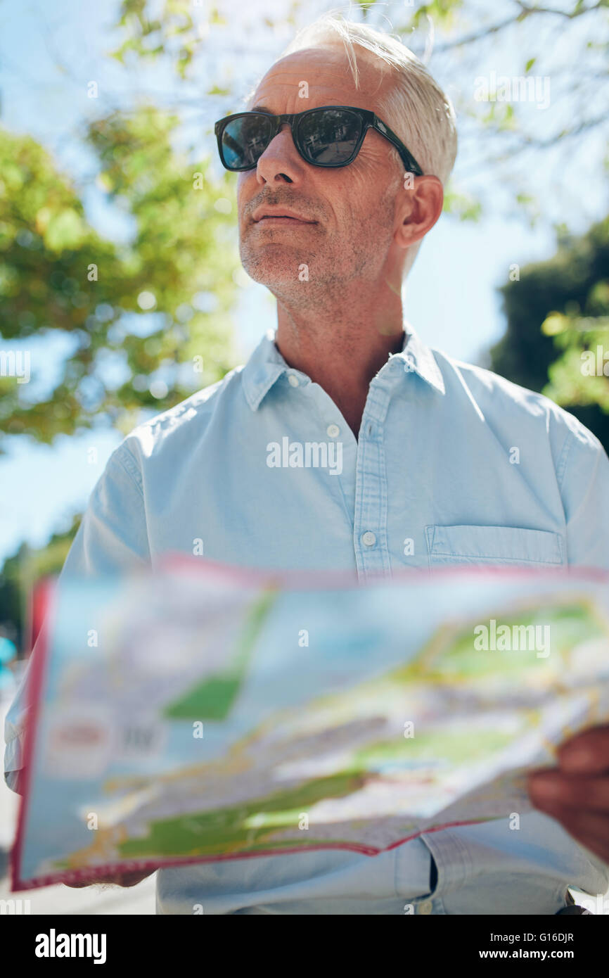 Close up shot of a mature man with a map while standing outdoors in the city on a summer day. Tourist holding a - Stock Image