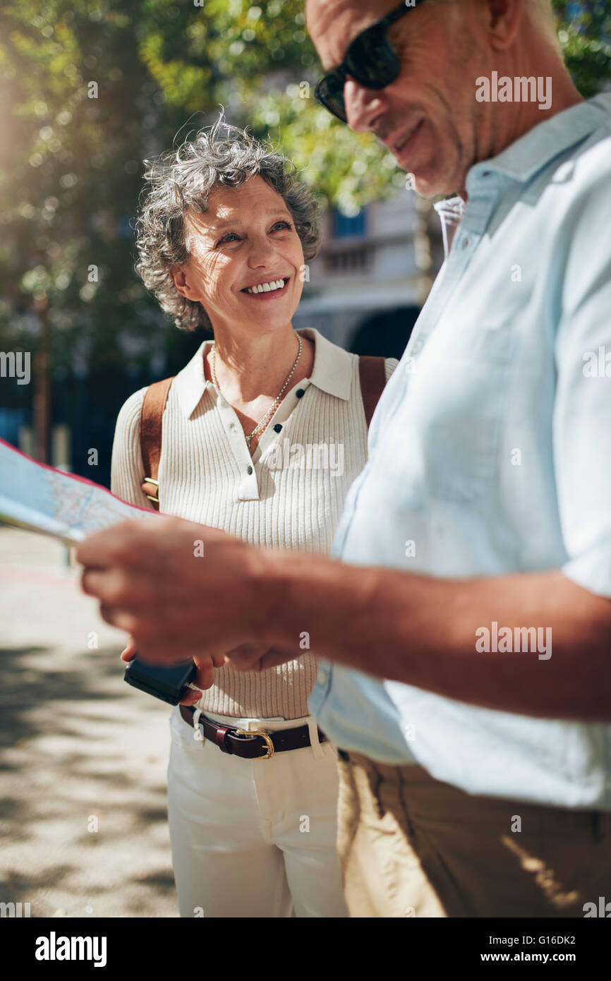 Mature couple using map while walking around a city. Man reading map and woman smiling. - Stock Image