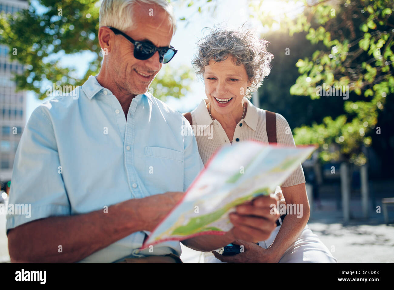 Elderly couple sitting outdoors and using city map. Happy retired couple looking for a destination on a city map. - Stock Image
