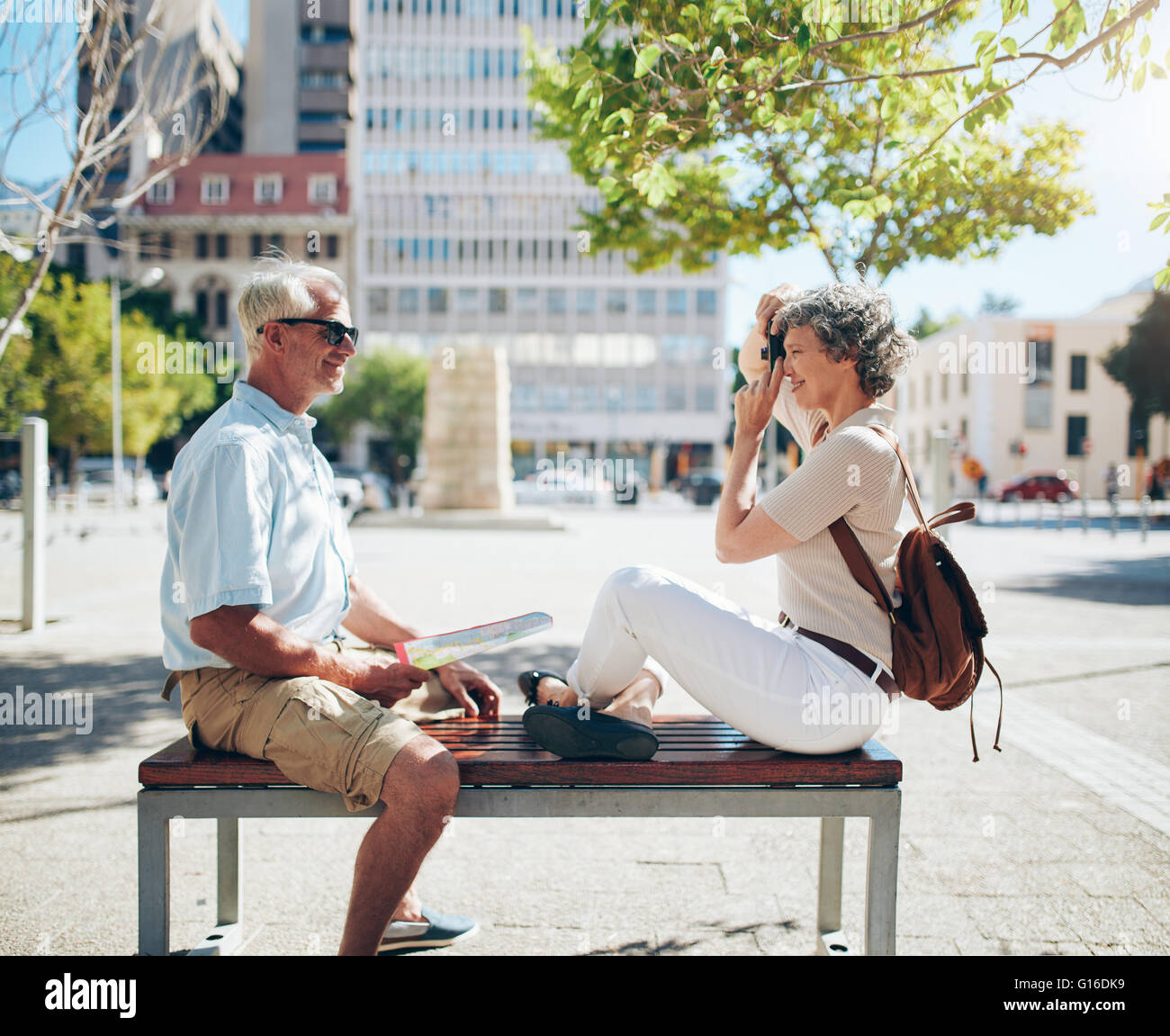 Side view of mature man sitting on bench and woman taking his photos with digital camera. Senior couple having fun - Stock Image