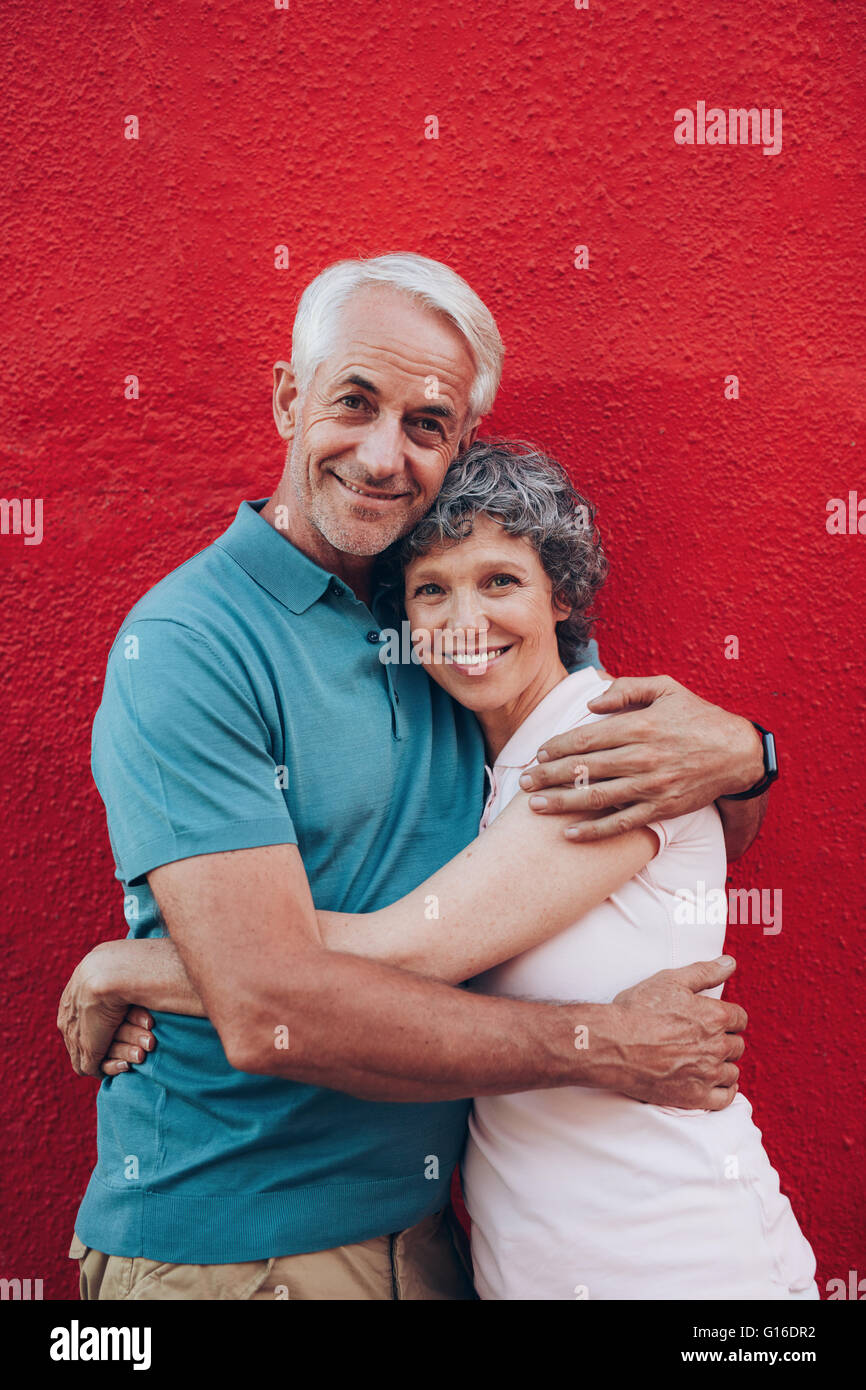 Portrait of beautiful senior couple embracing against red background. Loving mature couple standing together. - Stock Image