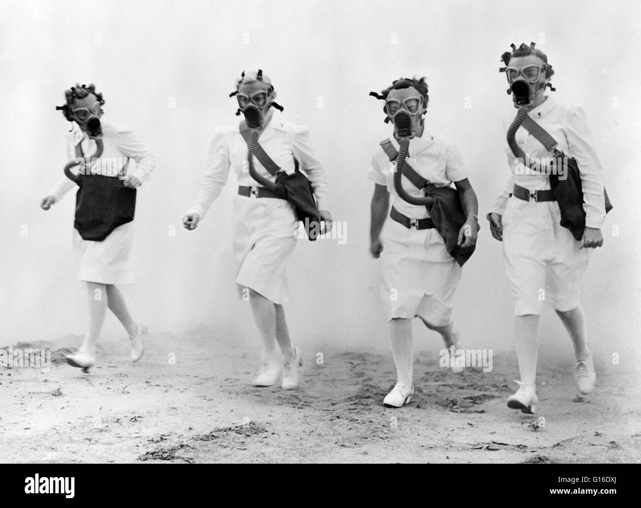 Nurses advancing through a cloud of smoke in a gas mask drill of the U.S. Army Air Forces Technical Training Command, - Stock Image