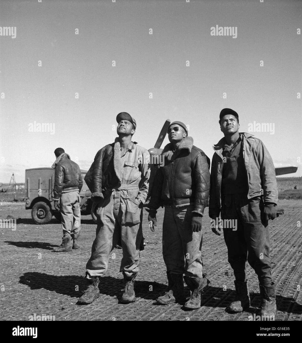 Entitled: 'Ground crew sweats in a mission' shows three Tuskegee airmen looking skyward, Ramitelli, Italy. - Stock Image