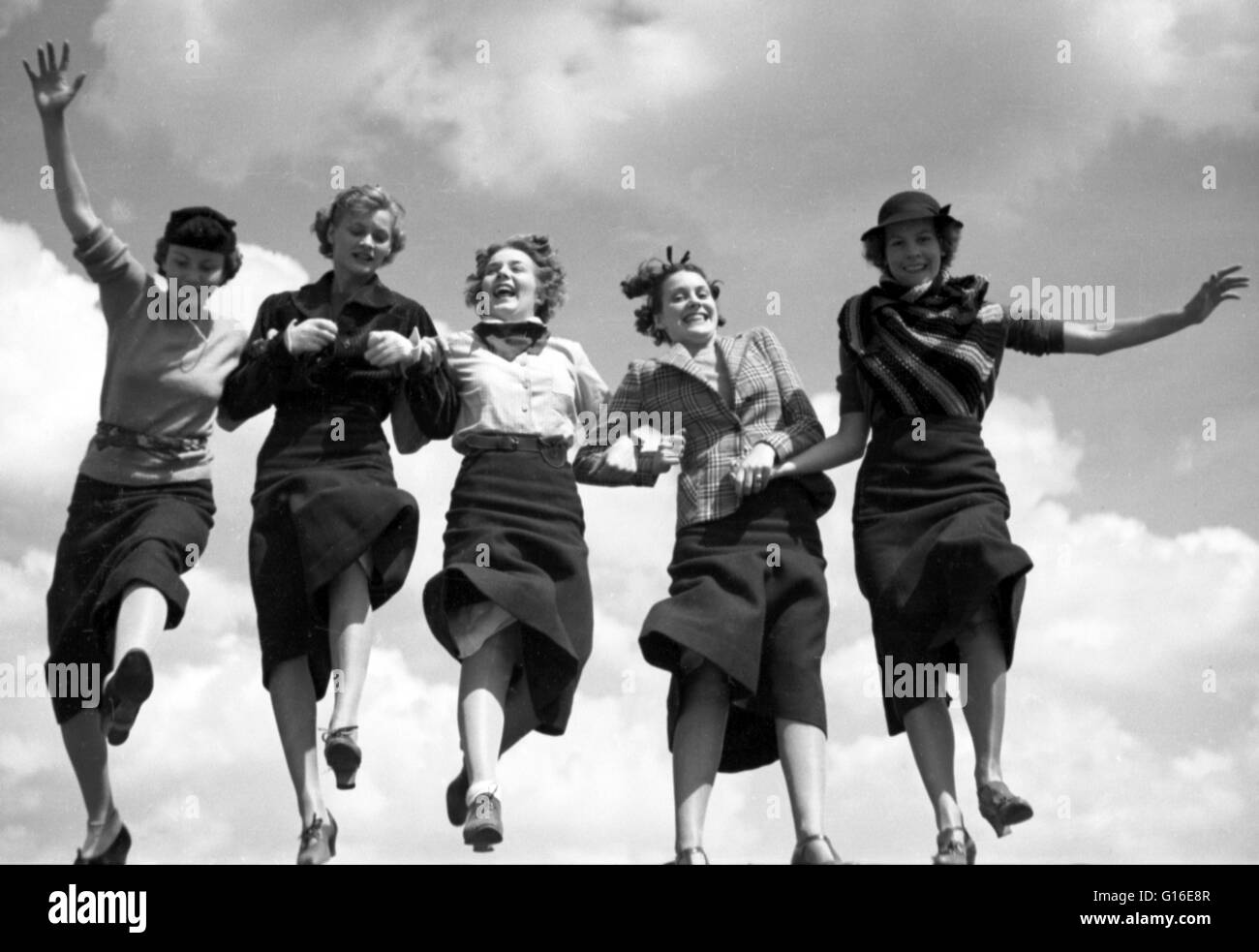 Entitled: 'Five women holding hands and walking together in a row, sky in background' photographed by Toni - Stock Image