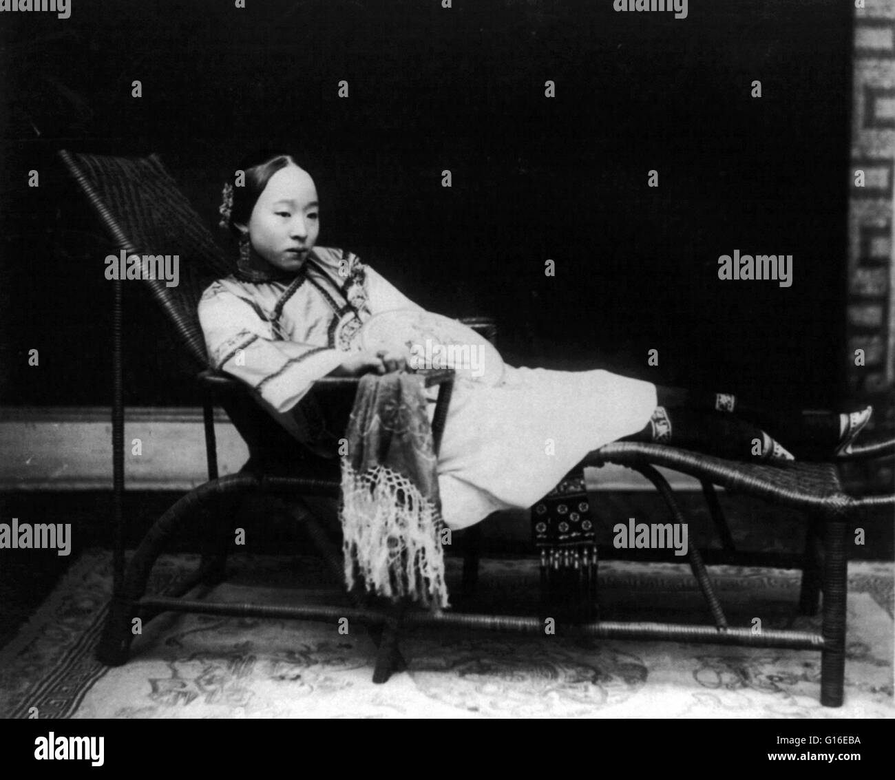 Entitled: 'Woman with bound feet reclining on chaise lounge, China. Circa 1890 and 1923. Foot binding (also - Stock Image