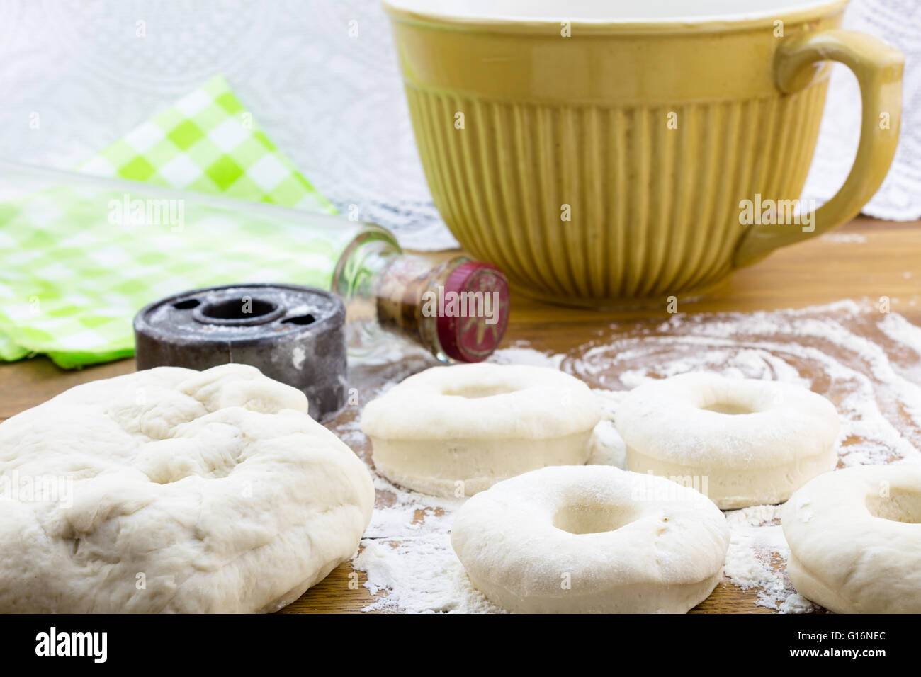 Risen dough nut dough on flowered wood table with vintage cutter and glass rolling pin Stock Photo